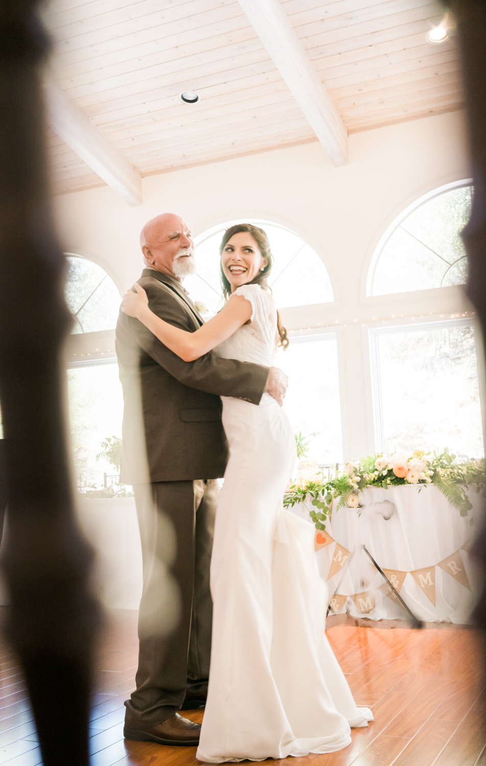 Bride dancing with her father - Photograph through the chair bars.