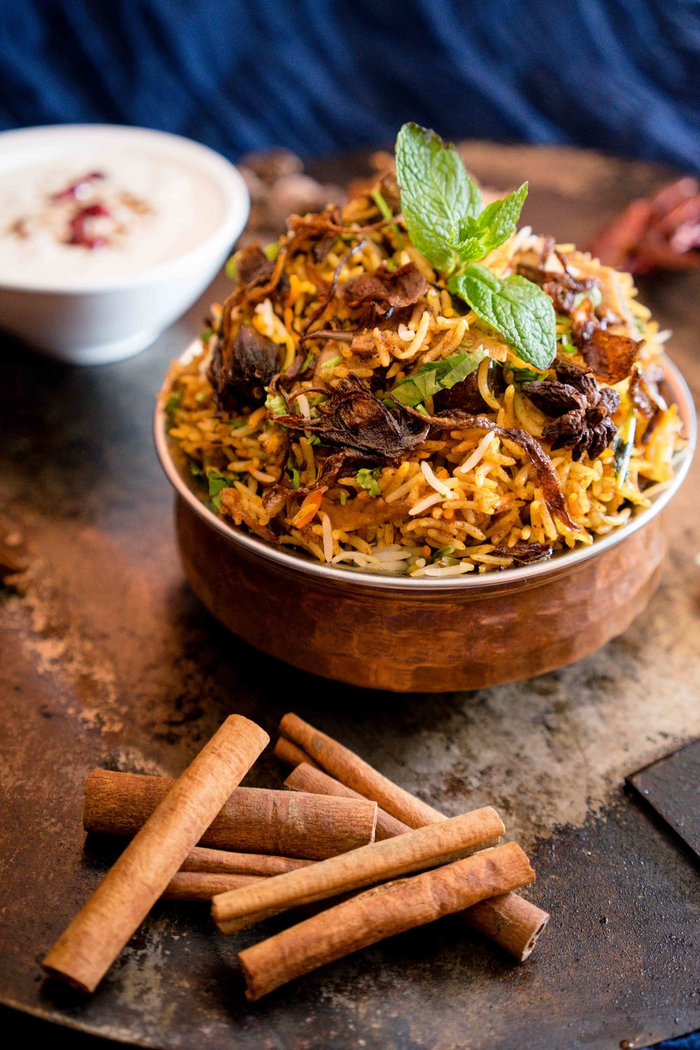 Goat Biryani - Slow cooked flavored rice with fresh herbs, saffron and rose water served with raita