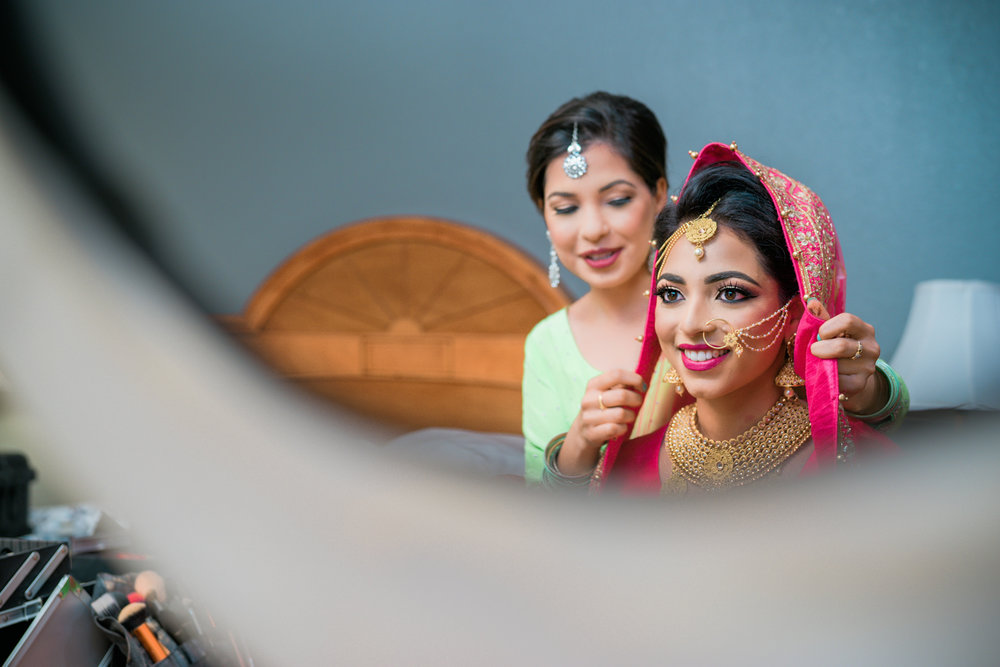 Bridesmaid helping the punjabi bride with the veil.