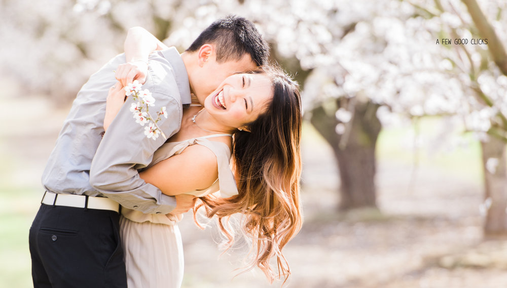 Smiling couples under the white trees of almond bloom