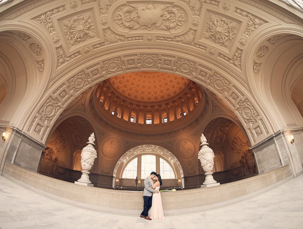 Couples photoshoot at the top balcony under the big arch at SF City Hall.