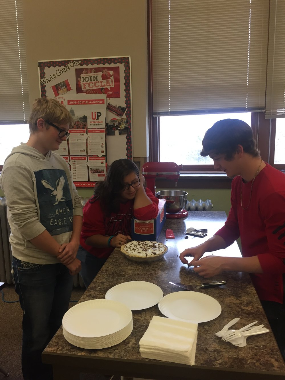 Bradyn Neubaum, Lydia Woods, and Tyler Francis preparing to serve their Chocolate Pie to the Foods class.