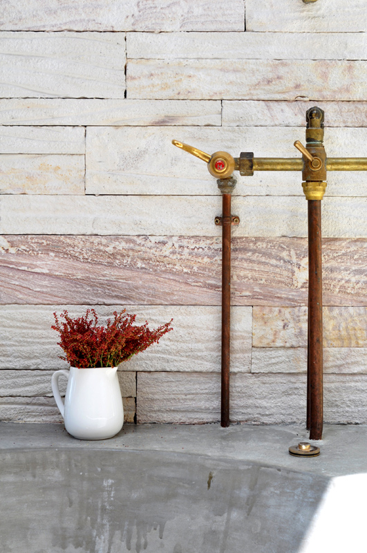 Rustic taps over the concrete bathtub.