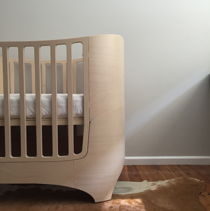 Crib sitting on cowhide rug