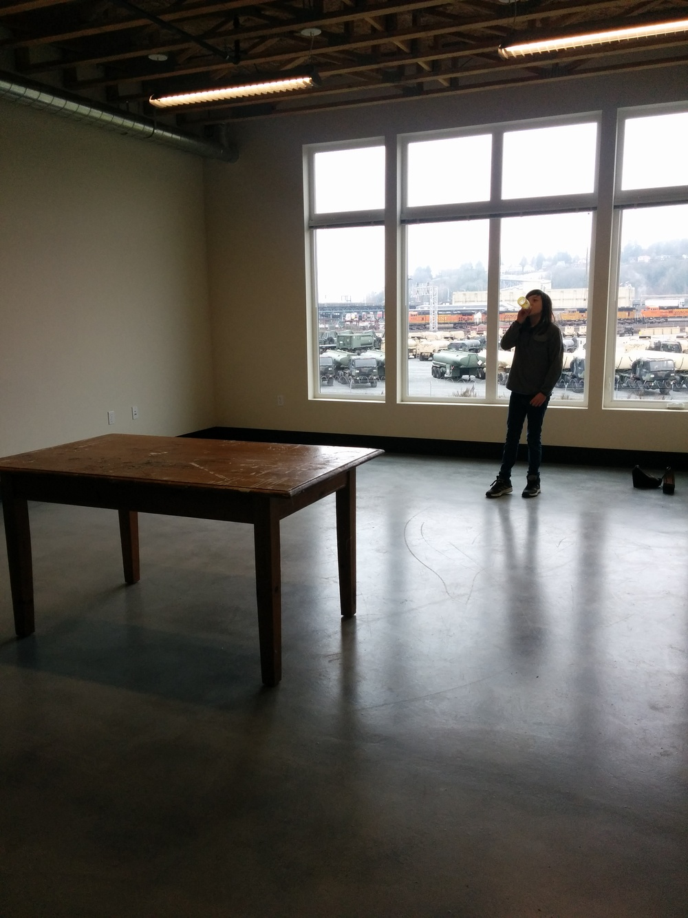 Julie Devine's daughter Eva in front of the big windows looking out across Interbay towards Magnolia.