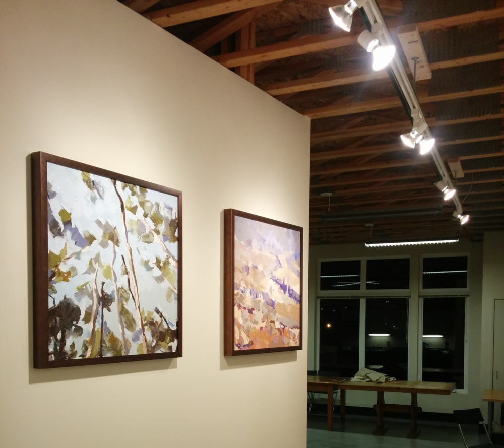 Julie Devine's  Taos Sky  and  Mt. Saint Helens, Territorial View  glow under the newly-installed halogen track lighting.