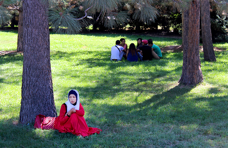 A woman sits under a tree in a park in Bishkek, Kyrgyzstan. © Jenne Raub