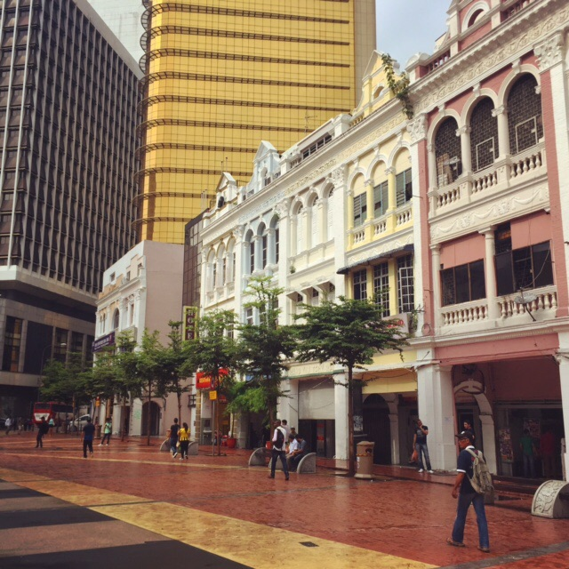 A pedestrianized street in Kuala Lumpur, where old colonial buildings are dwarfed by modern skyscrapers.