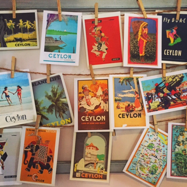 Postcards of old Ceylon travel posters hanging on a wall at The Empire Café in Kandy, Sri Lanka