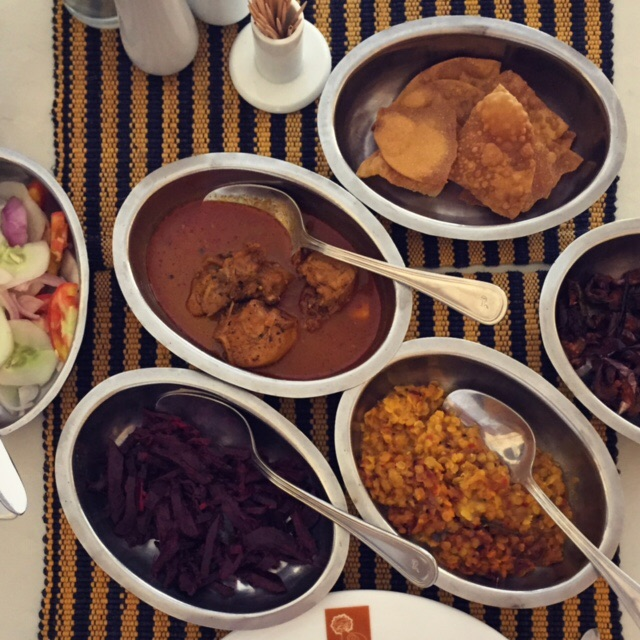 Dishes from the rice and curry spread at Dambulla Heritage Resthouse Cafe, including (clockwise from top) pappadam, zucchini with a spicy tomato paste, lentils, beets, salad and chicken curry.