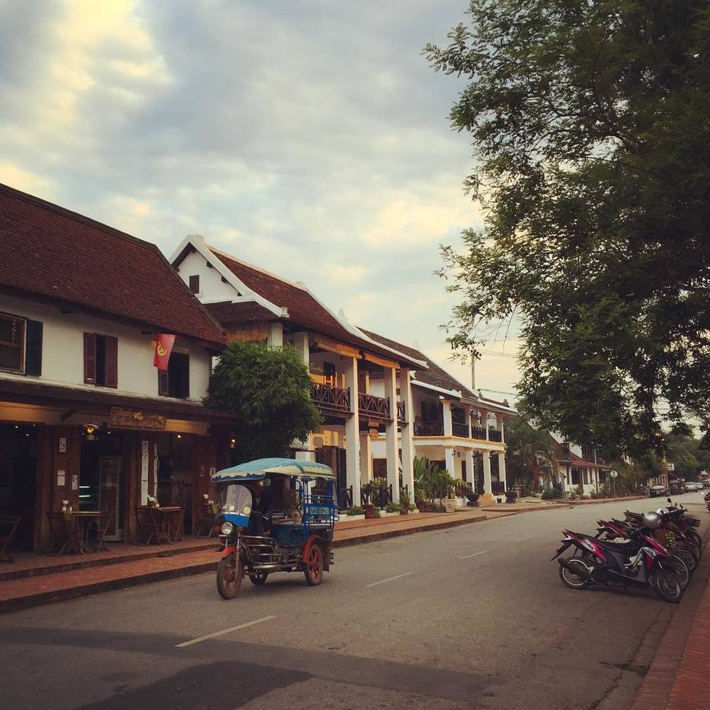 Pull up a chair at one of Luang Prabang's many street side cafés and watch life tuktuk by