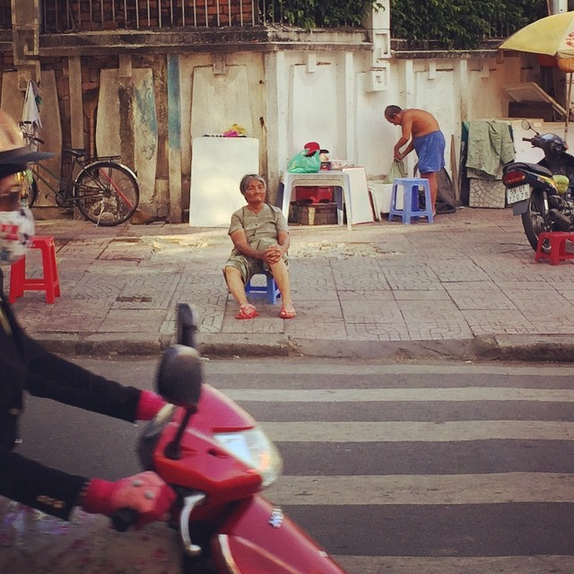 A woman in Ho Chi Minh City watches the world drift by