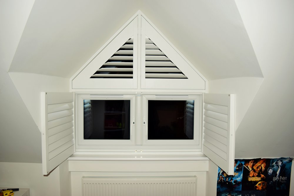 Triangle shapes window shutters in dormer