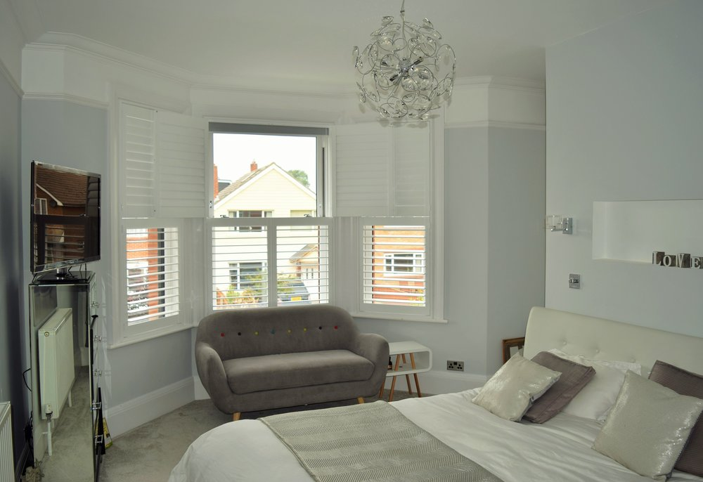 Tier on tier bay window shutters Bournemouth centre panels open.JPG