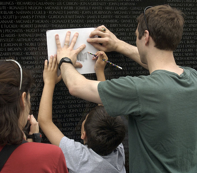 Visitors to the Vietnam Veterans Memorial Wall, take rubbings of the name, of a family member, 16 June 2003. Image source: US Navy 030616-N-9593R-142 Visitors to the Vietnam Veterans Memorial Wall, take rubbings of the name, of a family member.jpg, U.S. Navy photo by Chief Warrant Officer Seth Rossman, licensed under Public Domain Mark 1.0