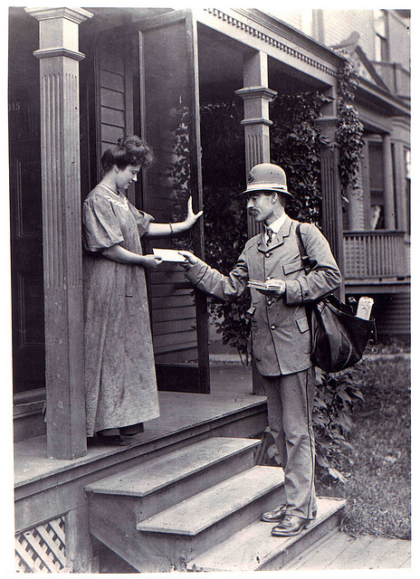 An unidentified city letter carrier delivers mail to a woman along his route, circa 1908. Image source: Photograph of letter carrier delivering mail (also Flickr Commons) by unknown photographer; from Smithsonian Institution, National Postal Museum; has no known copyright restrictions, fair use