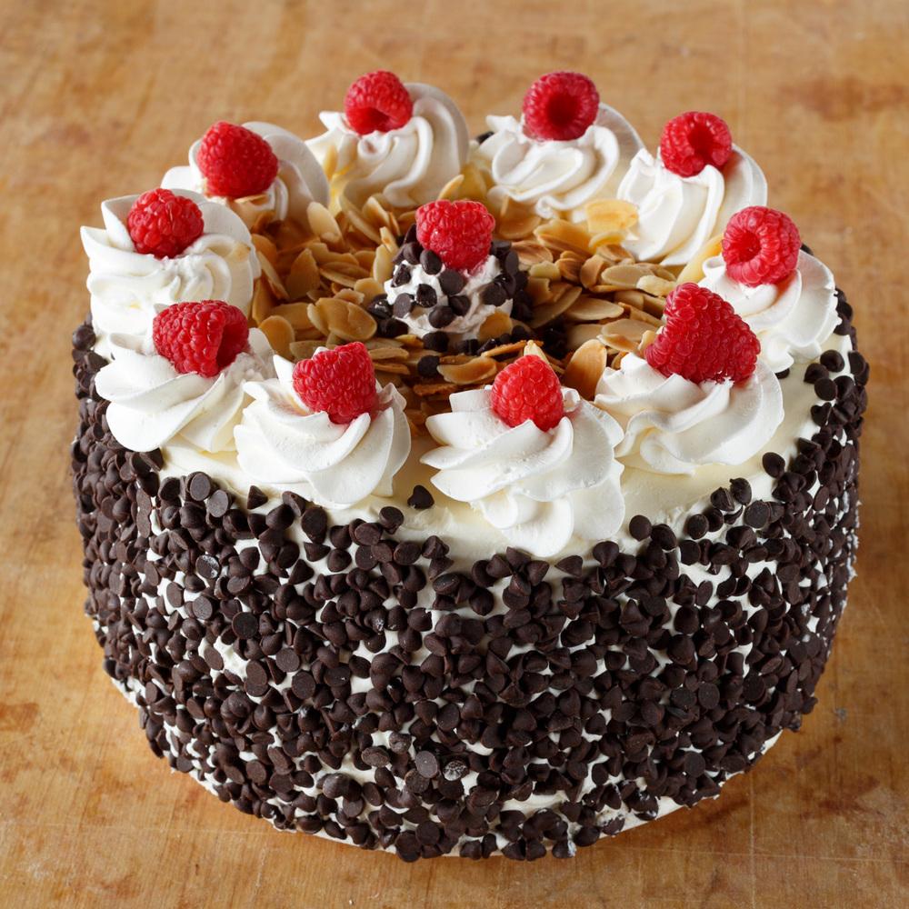 Fresh Raspberries And Toasted Walnuts On Whip Cream Cake