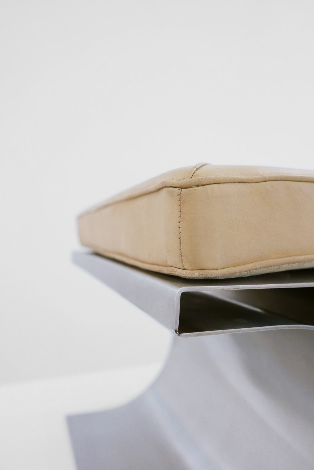 7. Micel Boyer, 'X' Stool, c. 1968, stainless steel and leather upholstery, 16H x 19.75W x 19.75D inches.jpg