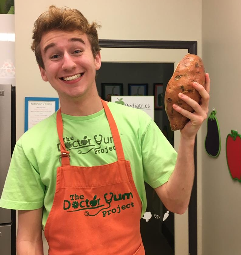 NutritionEd_Dr Yum team member Noah and sweet potato.jpg