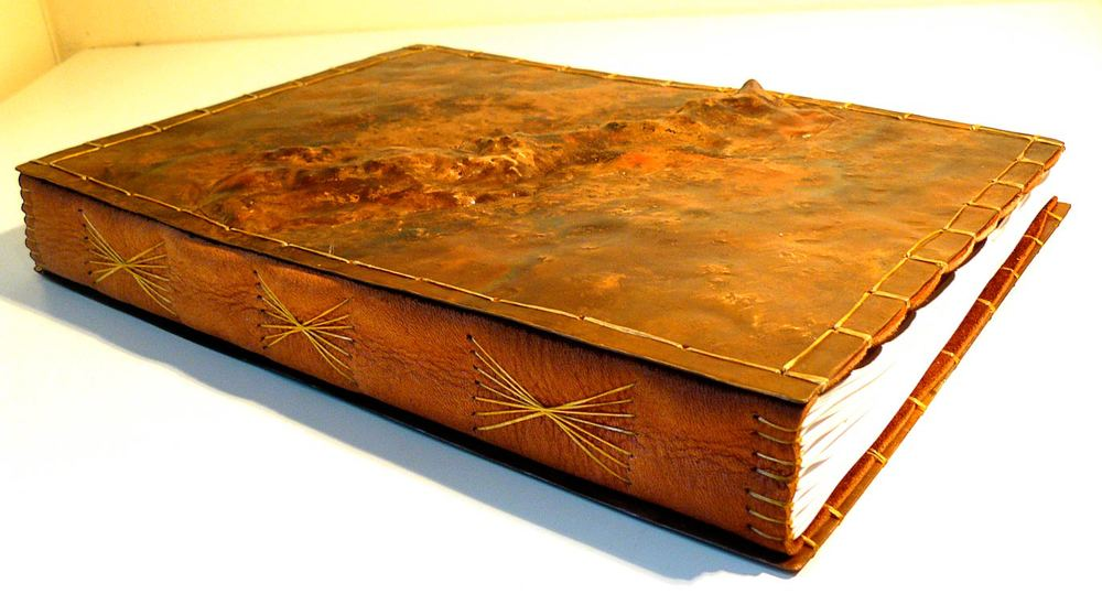 detail, hand-bound, leather and repoussé'd copper