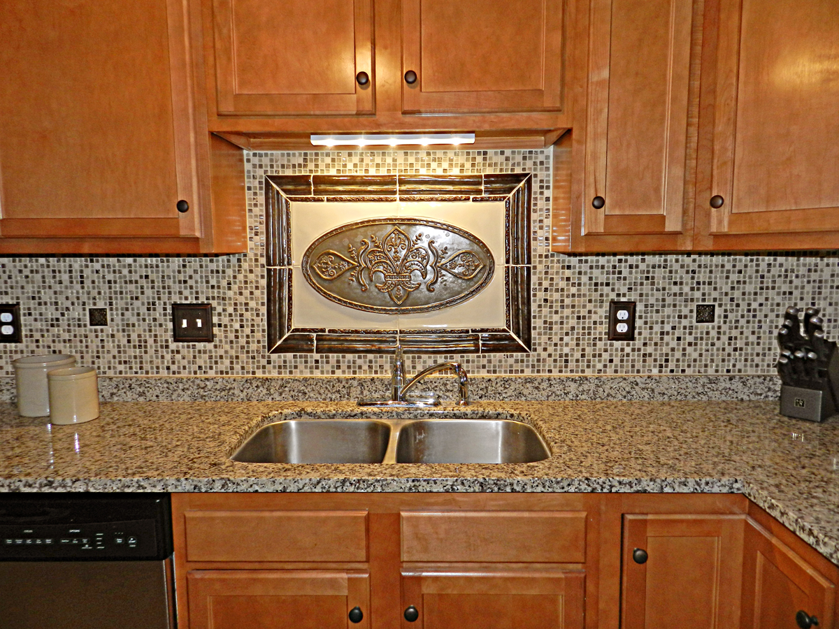 Stone and Glass mosaic tiles in the 'field', in addition 2x2 handmade tiles tie it all together as they are peppered throughout the backsplash.