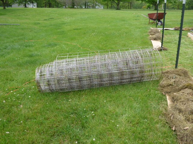 Reinforced mesh.  Hubby says it's cheap and it will keep the dogs out.