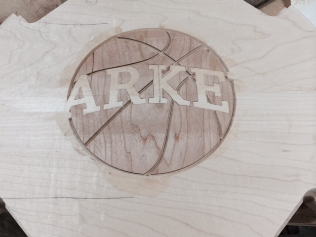 Next, pockets are cut for the walnut lines to create the markings on the basketball.  Care is taken not to cut into the maple lettering.