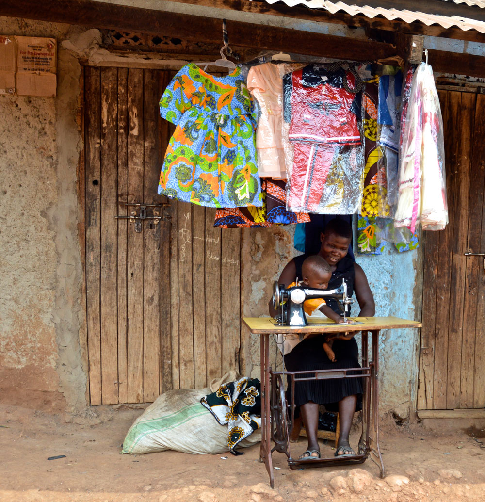 Lofisa sews with Hope, her daughter, in Namatala. Above her, are the handmade clothes she sells.
