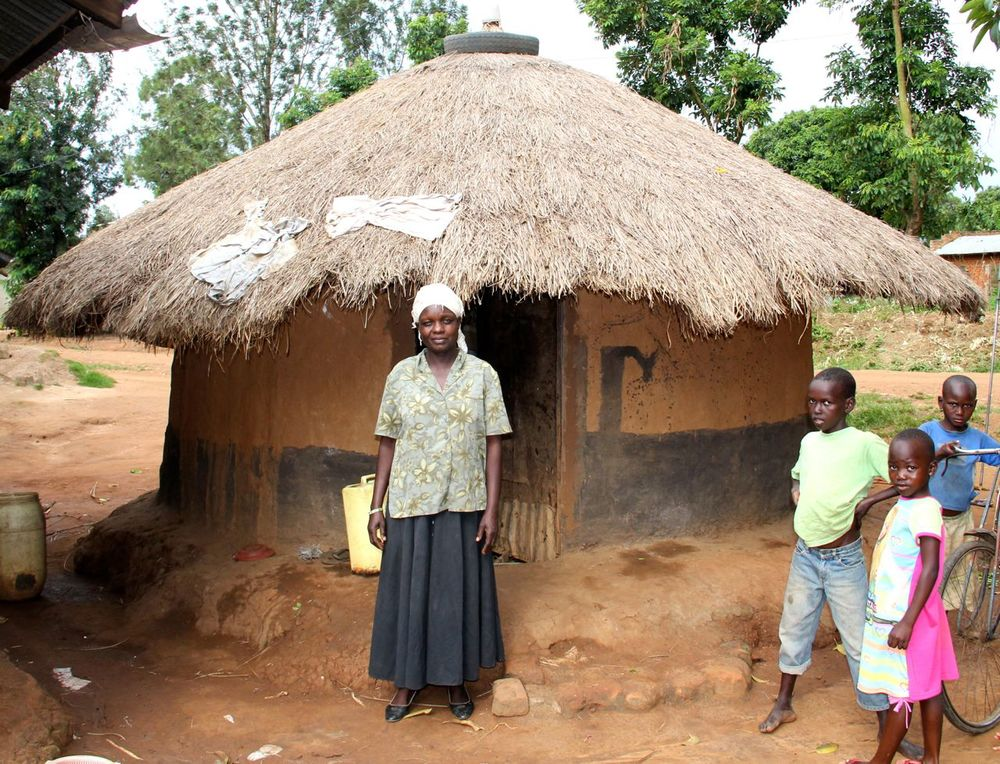 Magret stands in front of her home in Namatala.