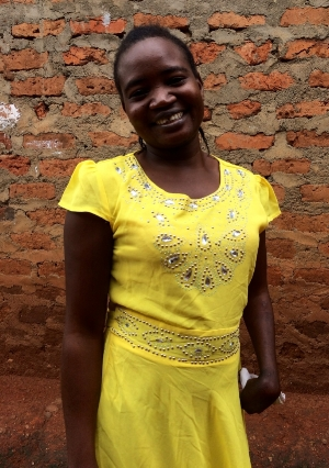 Amina wears her favorite yellow dress outside of her house in Namatala.
