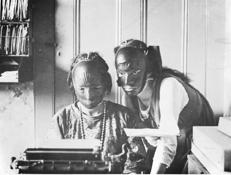 Rubber beauty masks, worn to remove wrinkles and blemishes; modelled by two women at a typewriter. Photograph, ca. 1921. From the  Wellcome  Library