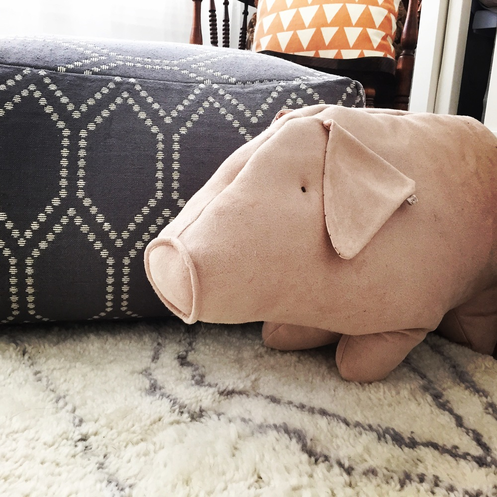 grey and white pouf + rug accented with this perfect blush-pink piggy found   here
