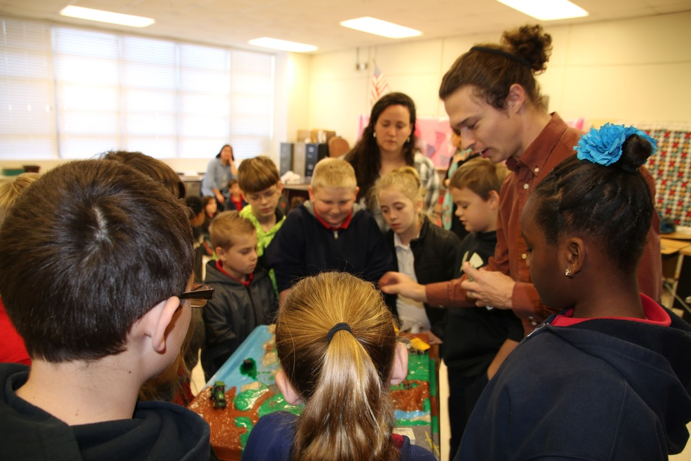 Program Coordinator Cade Kistler uses a hands on activity to educate students on sources of water pollution.