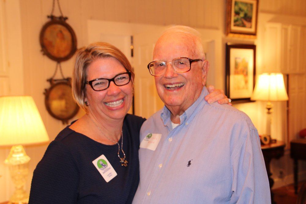 Executive Director Casi (kc) Callaway and Jack Greer exchange a laugh at the 20th Anniversary Kickoff Party in January of 2017 at the Greer's home.