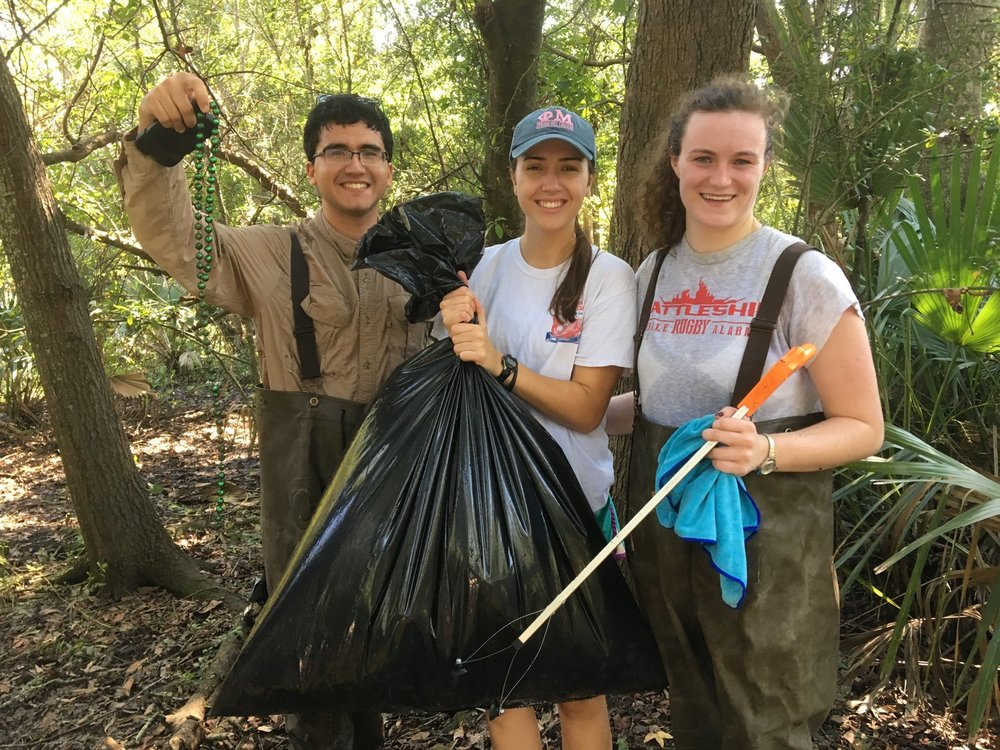 Above three Mobile Baykeeper interns remove Mardi Gras beads and other litter from the banks of One Mile Creek, a tributary to Mobile Bay via Three Mile Creek.