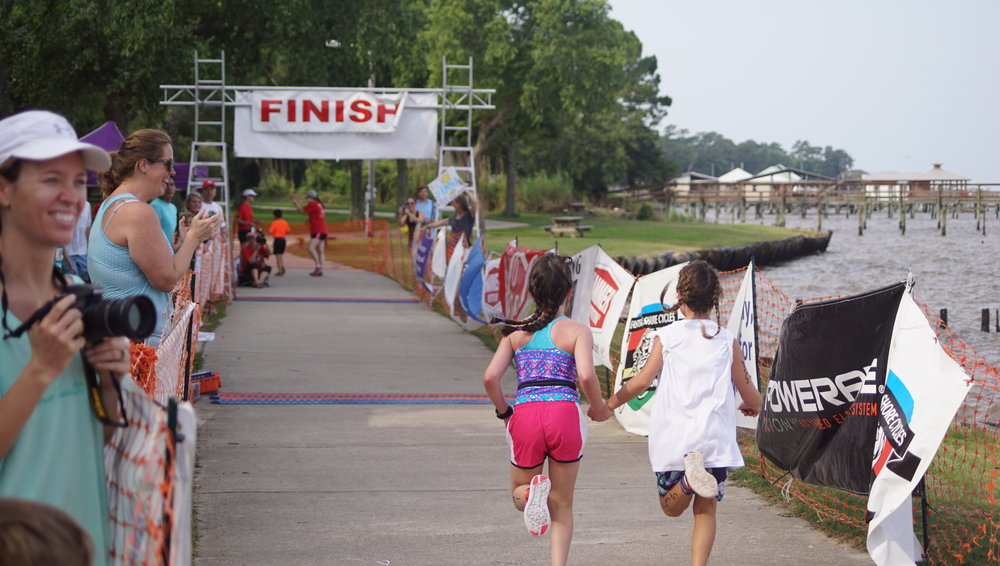 Kids understand true sportsmanship! Check out these two friends holding hands while crossing the finish line together.