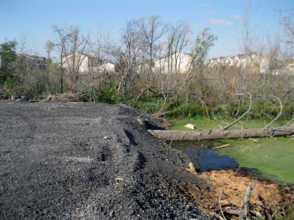 Asphalt parking lot illegally constructed in wetland.  (Photo Credit:    U.S. Army   )