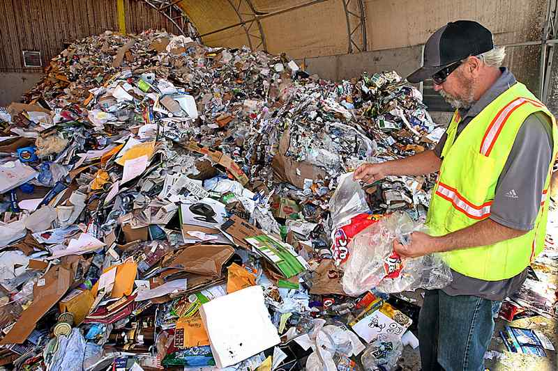 Craig Pearson, superintendent of Santa Cruz's Resource Recovery Facility, snatches individual plastic bags — the main source of problems — from a recently dumped load of recyclables on Dimeo Lane. (Dan Coyro — Santa Cruz Sentinel)