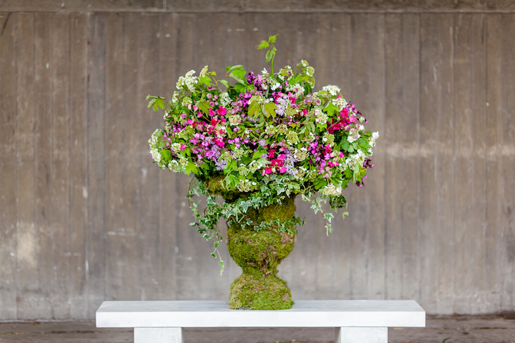 Day 3 of British Flowers Week 2016, featuring a moss covered urn overflowing with vibrant florals designed by Amanda Austin, presented to you by New Covent Garden Flower Market.