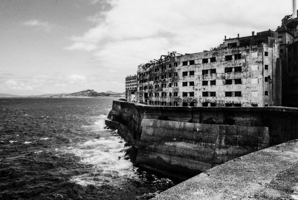 HASHIMA ISLAND, JAPAN   2001    Mid-century Japanese history never spoke much about Gunkanjima Island, an abandoned outpost 15km off the coast of Nagasaki.     Established in 1887 as a treasure for coal mining manufacturing, the 15-acre island's population reached its peak of 5,259 - one of the highest population densities ever recorded.  As petroleum gradually replaced coal in the post-WWII era, Gunkanjima was evacuated in 1974, leaving behind a ghost city untouched and off-limits for 35 years.