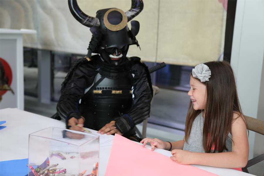 Samurai Sam joins in on an origami session with a new friend.