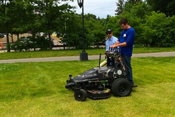 "Roth von Schmidall, turf manager, mows the lawn with the electric ""Stalker"" at Wellesley College."