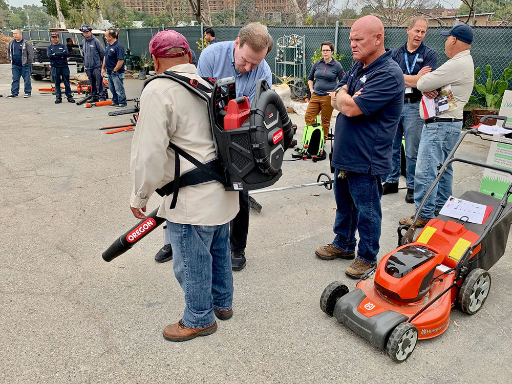 UCI HAS Grounds Supervisor Greg Haynes observes Matt Kennedy, Territory Sales Manager for Power Distributors, fit Oregon's new backpack leaf blower on one of his UCI crew.