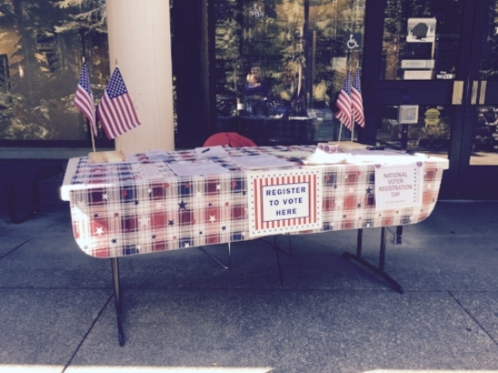 Table decorated with flags, stickers, pens, and forms for National Voter Registration Day. Photo courtesy of Valerie Walston.