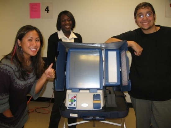Student poll workers pose with a touchscreen voting machine. Photo by Paulina Mysliwiec.