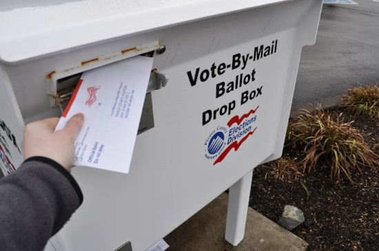 A voter inserts a ballot into one of Pierce County's drop off boxes. Photo by Whitney Rhodes.