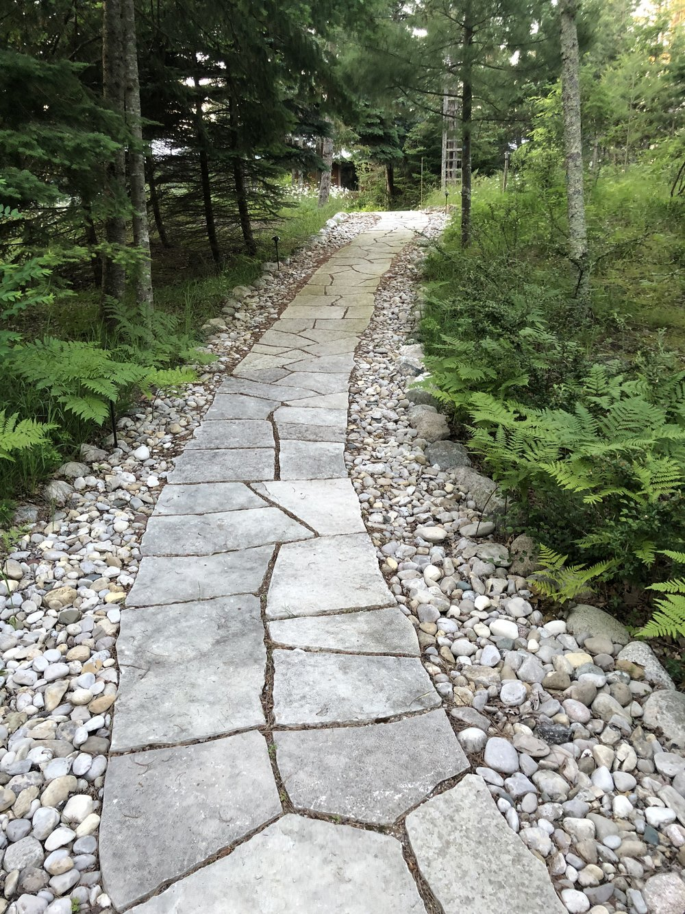 A beautifully hand-tooled stone path with lake-tumbled stone borders creates a beautiful entry path from parking to this home's entry.