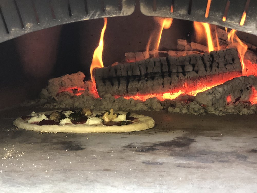 This amazing wood-fired pizza oven can get as hot as 600-700 degrees F!  It only takes a minute or two to cook a pizza!