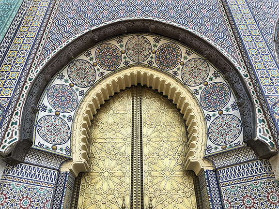 Entrance gate to the Royal Palace in Fez - articulated with detailed bronze doors, and multiple mosaic patterns in marble and precious stones.