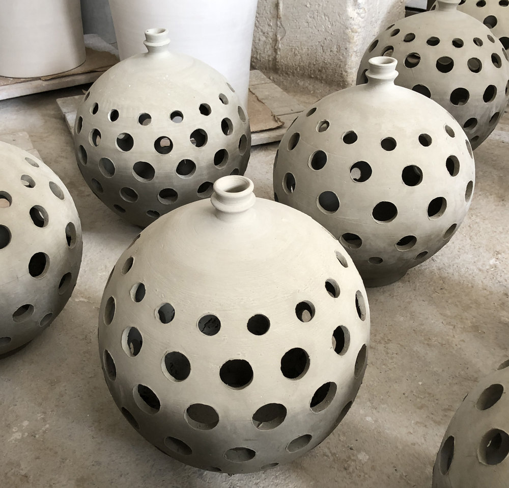 Decorative lanterns of all shapes and sizes are punched with holes to allow light to create patterns on adjacent walls. These beauties are in the process of curing prior to being glazed.